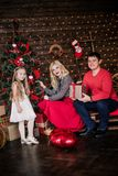 Η όμορφη νέα οικογένεια στο κόκκινο που έχει τη διασκέδαση μαζί για τις διακοπές Χριστουγέννων, που κάθονται σε ένα πάτωμα καθιστ Στοκ φωτογραφίες με δικαίωμα ελεύθερης χρήσης