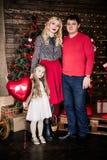 Η όμορφη νέα οικογένεια στο κόκκινο που έχει τη διασκέδαση μαζί για τις διακοπές Χριστουγέννων, που κάθονται σε ένα πάτωμα καθιστ Στοκ Εικόνες