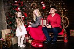 Η όμορφη νέα οικογένεια στο κόκκινο που έχει τη διασκέδαση μαζί για τις διακοπές Χριστουγέννων, που κάθονται σε ένα πάτωμα καθιστ Στοκ εικόνα με δικαίωμα ελεύθερης χρήσης