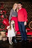 Η όμορφη νέα οικογένεια στο κόκκινο που έχει τη διασκέδαση μαζί για τις διακοπές Χριστουγέννων, που κάθονται σε ένα πάτωμα καθιστ Στοκ φωτογραφία με δικαίωμα ελεύθερης χρήσης