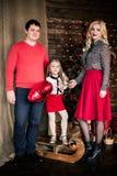 Η όμορφη νέα οικογένεια στο κόκκινο που έχει τη διασκέδαση μαζί για τις διακοπές Χριστουγέννων, που κάθονται σε ένα πάτωμα καθιστ Στοκ Εικόνα