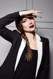 Η όμορφη νέα προκλητική γυναίκα brunette που φορά ένα σύντομο μοντέρνο σχέδιο φορεμάτων και ένα μοντέρνο σακάκι με τα άσπρα σύνορ Στοκ Φωτογραφία