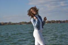 Η όμορφη νέα σγουρή γυναίκα έχει τη διασκέδαση από τη λίμνη Στοκ φωτογραφία με δικαίωμα ελεύθερης χρήσης