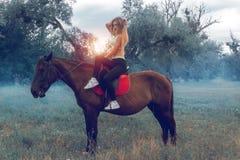 Η όμορφη νέα τοποθέτηση αναβατών τσίρκων σε ένα άλογο και κοιτάζει επίμονα Στοκ Φωτογραφίες