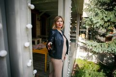 Η όμορφη νέα φθορά εγκύων γυναικών ντύνουν και το πουκάμισο δέρματος που στηρίζεται στον καφέ πάρκων πόλεων, μοντέρνος πυροβολισμ στοκ εικόνα