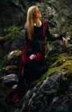 η όμορφη νεράιδα γυναικών με τη μακριά ξανθή τρίχα σε μια ιστορική εσθήτα κάθεται amids τα μουγκρητά κάλυψε τους βράχους Στοκ Εικόνες