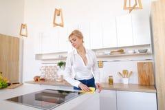 Η όμορφη νοικοκυρά ακολουθεί επιμελώς τη διαταγή και σκουπίζει την επιφάνεια, Στοκ φωτογραφία με δικαίωμα ελεύθερης χρήσης