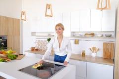 Η όμορφη νοικοκυρά ακολουθεί επιμελώς τη διαταγή και σκουπίζει την επιφάνεια, Στοκ Εικόνες