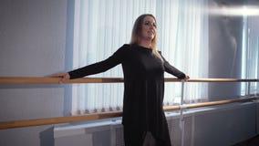 Η όμορφη νοικοκυρά κάνει ένα workout πρίν χορεύει στην μπάρα μπαλέτου σε ένα στούντιο χορού Μια ενήλικη γυναίκα που κάνει τις στά φιλμ μικρού μήκους
