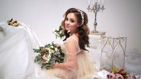 Η όμορφη νύφη κάθεται από τα γαμήλια φορέματα, γύρω από τις ανθοδέσμες και το ντεκόρ Εξετάζει άμεσα τη κάμερα, μεγάλη φιλμ μικρού μήκους