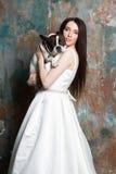 Η όμορφη νύφη κρατά ένα σκυλί Στοκ Εικόνες