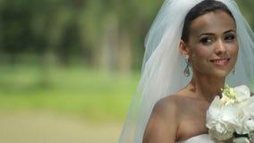 Η όμορφη νύφη κρατά μια ανθοδέσμη μπροστά από το πάρκο ευτυχής γάμος ημέρας απόθεμα βίντεο
