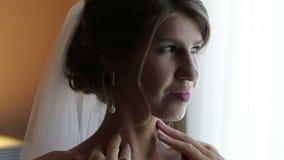 Η όμορφη νύφη με τη σκοτεινή σγουρή τρίχα βάζει στο λαμπιρίζοντας σκουλαρίκι απόθεμα βίντεο