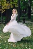 Η όμορφη νύφη περιστρέφει γύρω από την στο χορό η γυναίκα θέτει στο κυματίζοντας φόρεμα υπαίθρια _ στοκ φωτογραφία