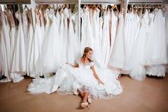 Η όμορφη νύφη προσπαθεί σε ένα κομψό γαμήλιο φόρεμα στοκ εικόνες