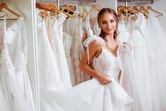 Η όμορφη νύφη προσπαθεί σε ένα κομψό γαμήλιο φόρεμα στοκ εικόνες με δικαίωμα ελεύθερης χρήσης