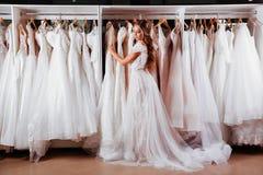Η όμορφη νύφη προσπαθεί σε ένα κομψό γαμήλιο φόρεμα στοκ εικόνα με δικαίωμα ελεύθερης χρήσης
