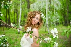 Η όμορφη νύφη σε ένα άσπρο φόρεμα στην άνθιση καλλιεργεί την άνοιξη Στοκ Εικόνες