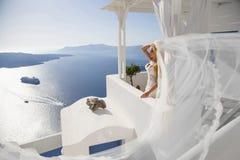 Η όμορφη νύφη σε ένα γαμήλιο φόρεμα σε Santorini στην Ελλάδα Στοκ Φωτογραφίες