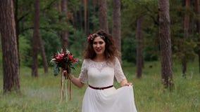 Η όμορφη νύφη σε ένα εκλεκτής ποιότητας φόρεμα με τη χρωματισμένη ανθοδέσμη στο θερινό δάσος πηγαίνει στη κάμερα και το χαμόγελο απόθεμα βίντεο