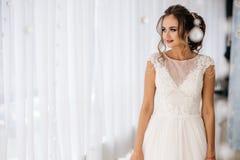 Η όμορφη νύφη στο άσπρο γαμήλιο φόρεμα στέκεται στο δωμάτιο μπουντουάρ Στοκ Εικόνες