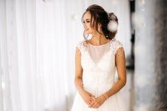 Η όμορφη νύφη στο άσπρο γαμήλιο φόρεμα στέκεται στο φωτεινό δωμάτιο και το χαμόγελο Στοκ φωτογραφία με δικαίωμα ελεύθερης χρήσης