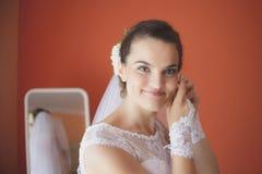 Η όμορφη νύφη στο άσπρο γαμήλιο φόρεμα βάζει στο σκουλαρίκι Στοκ Φωτογραφίες