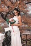 Η όμορφη νύφη στο κομψό άσπρο φόρεμα που κρατά μια ανθοδέσμη των λουλουδιών παραδίδει μέσα το πάρκο φθινοπώρου Νύφη Νέο πρότυπο μ Στοκ Φωτογραφία