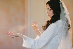 Η όμορφη νύφη ψεκάζει το άρωμα σε διαθεσιμότητα Στοκ φωτογραφία με δικαίωμα ελεύθερης χρήσης