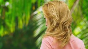 Η όμορφη ξανθή γυναίκα αγγίζει την τρίχα της στη φύση υποστηρίξτε την όψη Έννοια επεξεργασίας τρίχας απόθεμα βίντεο