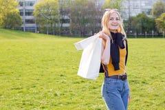 Η όμορφη ξανθή γυναίκα απολαμβάνει τις αγορές Καταναλωτισμός, χλεύη αγορών επάνω, έννοια τρόπου ζωής στοκ εικόνες
