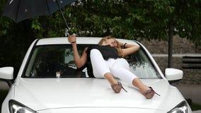 Η όμορφη ξανθή γυναίκα βρίσκεται στην κουκούλα του άσπρου αυτοκινήτου με την ομπρέλα στη βροχερή θερινή ημέρα κίνηση αργή φιλμ μικρού μήκους