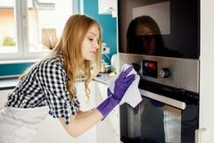 Η όμορφη ξανθή γυναίκα γυαλίζει το φούρνο ανοξείδωτου Στοκ Εικόνες