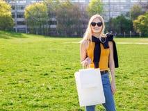 Η όμορφη ξανθή γυναίκα με τα γυαλιά ηλίου απολαμβάνει τις αγορές Καταναλωτισμός, χλεύη αγορών επάνω, έννοια τρόπου ζωής στοκ εικόνα
