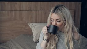 Η όμορφη ξανθή γυναίκα που κρατά το κεραμικό φλυτζάνι του τσαγιού ή του καφέ απολαμβάνει Χρόνος τσαγιού στο δωμάτιο κρεβατιών Η ε φιλμ μικρού μήκους