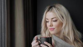 Η όμορφη ξανθή γυναίκα που κρατά το κεραμικό φλυτζάνι του τσαγιού ή του καφέ απολαμβάνει Χρόνος τσαγιού στο δωμάτιο κρεβατιών Η ε απόθεμα βίντεο