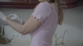 Η όμορφη ξανθή γυναίκα που φορά τα γάντια πλυσίματος των πιάτων και αρχίζει να πλένει τα πιάτα απόθεμα βίντεο