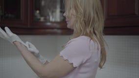 Η όμορφη ξανθή γυναίκα που φορά τα γάντια πλυσίματος των πιάτων και αρχίζει να πλένει τα πιάτα φιλμ μικρού μήκους