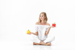 Η όμορφη ξανθή γυναίκα στην άσπρη μπλούζα επιλέγει το κίτρινο ή κόκκινο πιπέρι κουδουνιών υγεία σιτηρεσίου Στοκ εικόνες με δικαίωμα ελεύθερης χρήσης