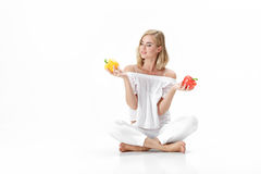Η όμορφη ξανθή γυναίκα στην άσπρη μπλούζα επιλέγει το κίτρινο ή κόκκινο πιπέρι κουδουνιών υγεία σιτηρεσίου Στοκ Εικόνα