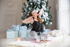Η όμορφη ξανθή γυναίκα τεντώνει, κοιμήθηκε καλά και είναι έτοιμη για μια νέα ημέρα, όμορφο νέο πρωί έτους, Χριστούγεννα Breakfas Στοκ φωτογραφία με δικαίωμα ελεύθερης χρήσης