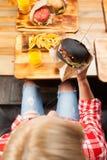 Η όμορφη ξανθή γυναίκα τρώει Burger βόειου κρέατος τη τοπ άποψη γωνίας Στοκ εικόνες με δικαίωμα ελεύθερης χρήσης