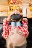 Η όμορφη ξανθή γυναίκα τρώει Burger βόειου κρέατος τη τοπ άποψη γωνίας Στοκ Εικόνες