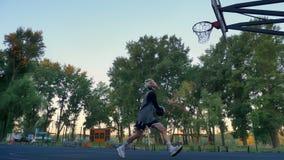 Η όμορφη ξανθή θηλυκή ρίψη φορέων στη στεφάνη καλαθοσφαίρισης, σφαίρα χτυπά το δαχτυλίδι, που παίζει στο πάρκο κατά τη διάρκεια τ απόθεμα βίντεο