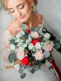 Η όμορφη ξανθή νύφη κρατά τη γαμήλια ανθοδέσμη των τριαντάφυλλων Στοκ Φωτογραφίες