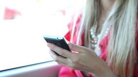 Η όμορφη ξανθή συνεδρίαση κοριτσιών στο τραμ, κλείνει επάνω σε κινητό, τηλέφωνο, κύτταρο απόθεμα βίντεο