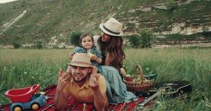 Η όμορφη οικογένεια στις συγκινήσεις πικ-νίκ που κοιτάζουν στη κάμερα που χαμογελά και έχει τα ευτυχή πρόσωπα φιλμ μικρού μήκους