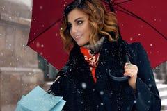 Η όμορφη οδός χιονιού γυναικών αγοράζει παρουσιάζει το νέο έτος Χριστουγέννων Στοκ Φωτογραφίες