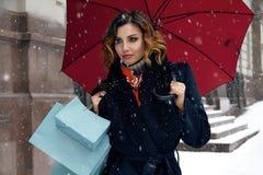 Η όμορφη οδός χιονιού γυναικών αγοράζει παρουσιάζει το νέο έτος Χριστουγέννων Στοκ εικόνες με δικαίωμα ελεύθερης χρήσης