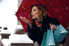 Η όμορφη οδός χιονιού γυναικών αγοράζει παρουσιάζει το νέο έτος Χριστουγέννων Στοκ φωτογραφία με δικαίωμα ελεύθερης χρήσης